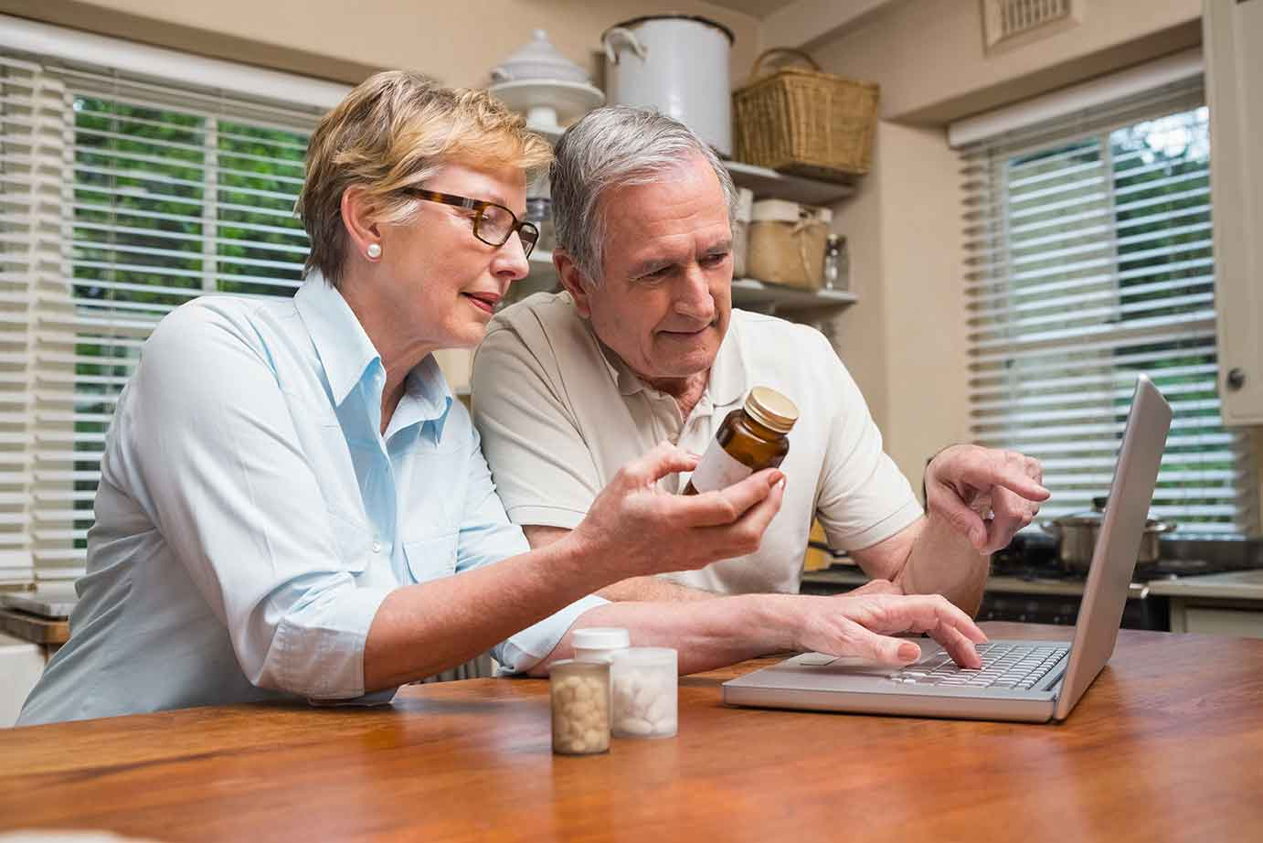 Lovely senior couple looking up RX prices on computer